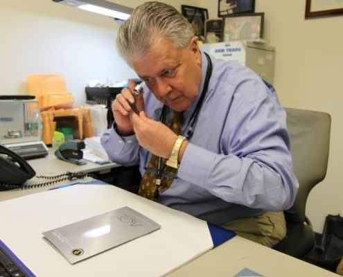 Joseph Menzie at his desk examining colored gemstones